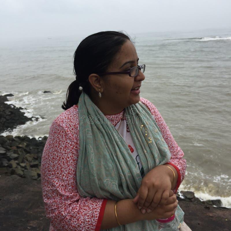 Uma mulher indiana nova em uma praia rochosa em Kunoor imagens de stock royalty free