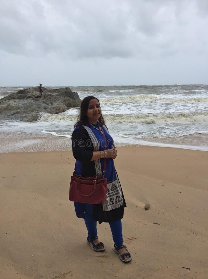 Uma mulher indiana nova que levanta na praia de Kundapura fotografia de stock royalty free