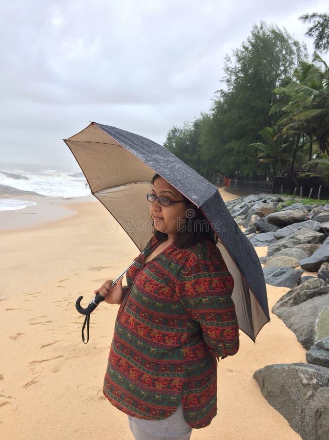 Uma mulher indiana nova sob o guarda-chuva na praia de Kundapura fotos de stock royalty free