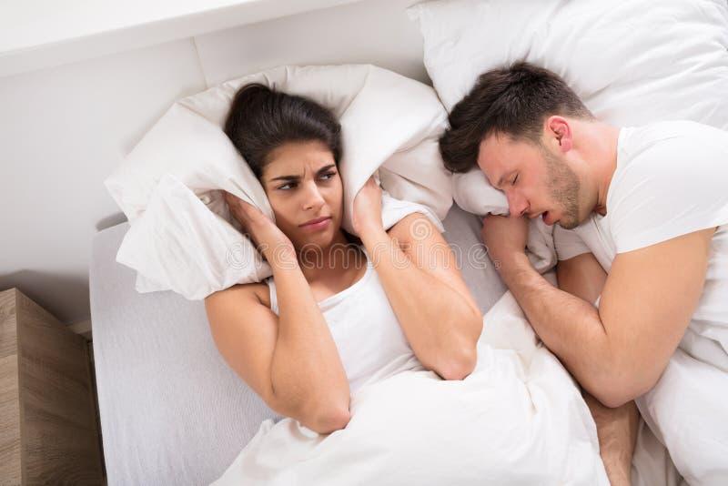 Uma mulher irritada com o marido ressonando na cama fotografia de stock royalty free