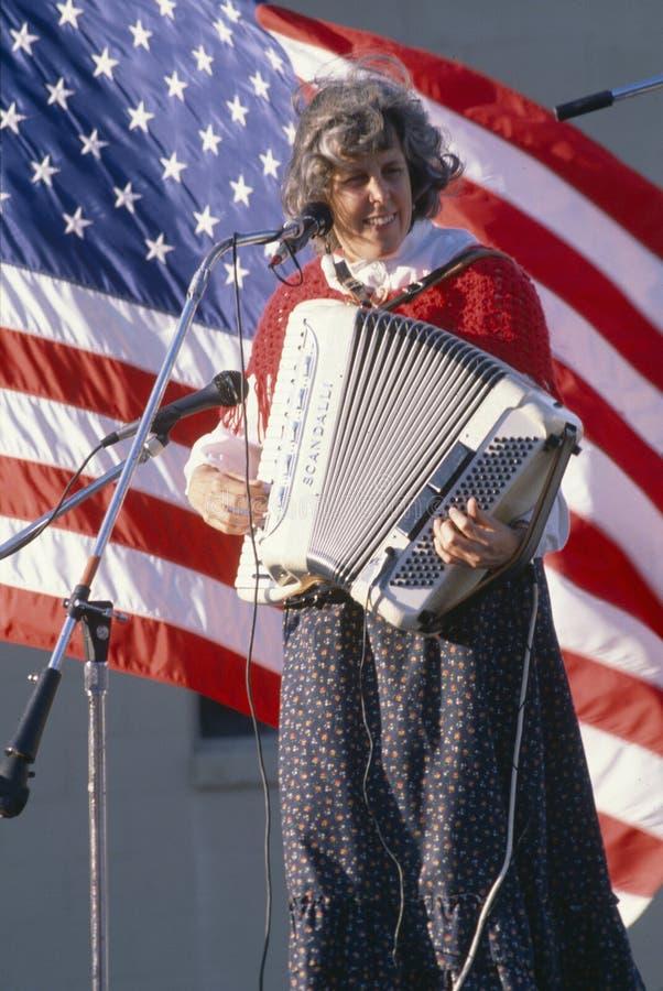 Uma mulher joga o acordeão na frente da bandeira americana, Hannibal, MO fotografia de stock royalty free
