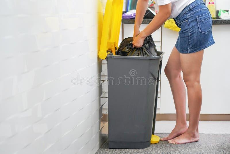Uma mulher joga o lixo no lixo na cozinha fotos de stock