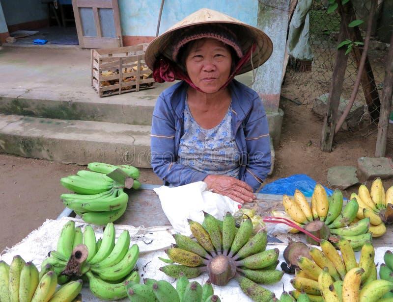 Uma mulher local nas bananas de venda vietnamianas tradicionais no mercado imagens de stock