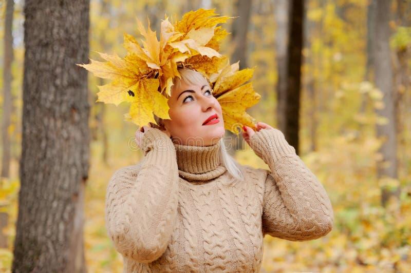 Uma mulher loura bonita do grande tamanho em uma grinalda de suportes amarelos das folhas de outono na floresta em um fundo amare imagens de stock
