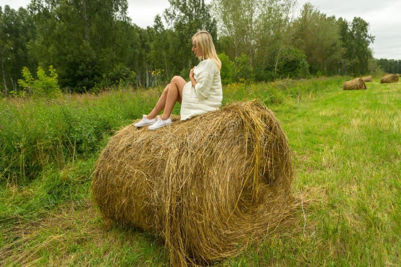 Uma mulher loura bonita na em um revestimento de lã feito malha branco senta-se imagens de stock royalty free