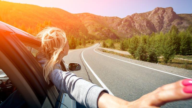 Uma mulher loura com seu dirige para fora a janela fotografia de stock royalty free