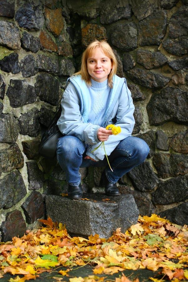 Uma mulher loura de sorriso nova com os dentes-de-leão amarelos em suas mãos senta-se perto de uma parede de pedra fotos de stock