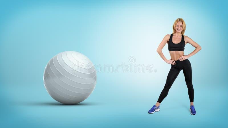 Uma mulher loura do ajuste novo está com mãos em seus quadris perto de uma grande bola de prata do exercício imagens de stock