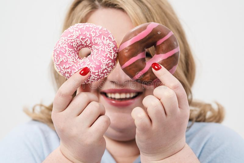 Uma mulher loura gorda, gorda em um fundo branco, guardando anéis de espuma vitrificados cor-de-rosa e uma maçã vermelha foto de stock