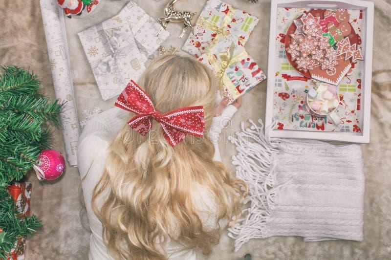 Uma mulher loura nova bonita, com uma curva em sua cabeça, encontra-se no assoalho e envolve-se presentes do Natal Preparações do imagem de stock royalty free