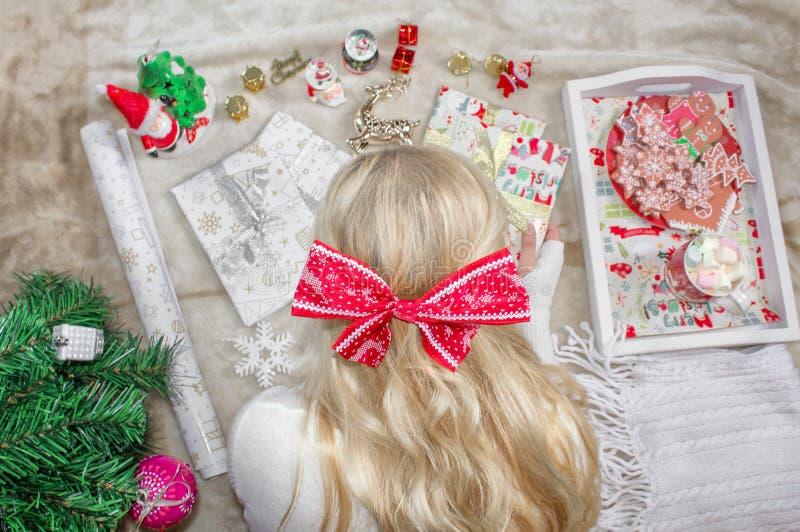 Uma mulher loura nova bonita, com uma curva em sua cabeça, encontra-se no assoalho e envolve-se presentes do Natal Preparações do fotografia de stock