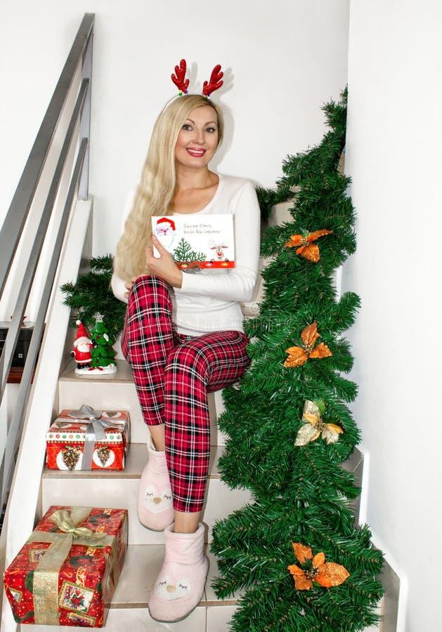 Uma mulher loura nova bonita em pijamas do Natal e com os chifres da rena, sentando-se nas etapas, decoradas com ramos do abeto imagem de stock royalty free