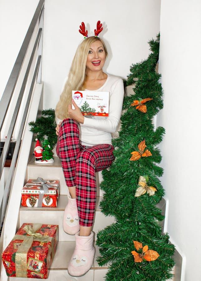 Uma mulher loura nova bonita em pijamas do Natal e com os chifres da rena, sentando-se nas etapas, decoradas com ramos do abeto fotografia de stock royalty free