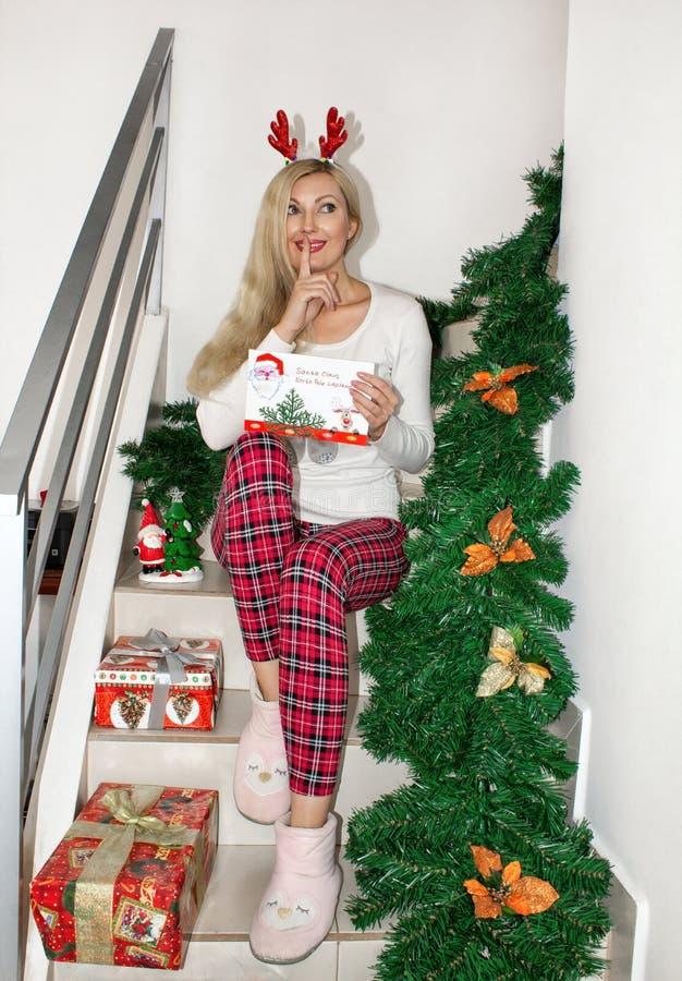 Uma mulher loura nova bonita em pijamas do Natal e com os chifres da rena, sentando-se nas etapas, decoradas com ramos do abeto imagem de stock