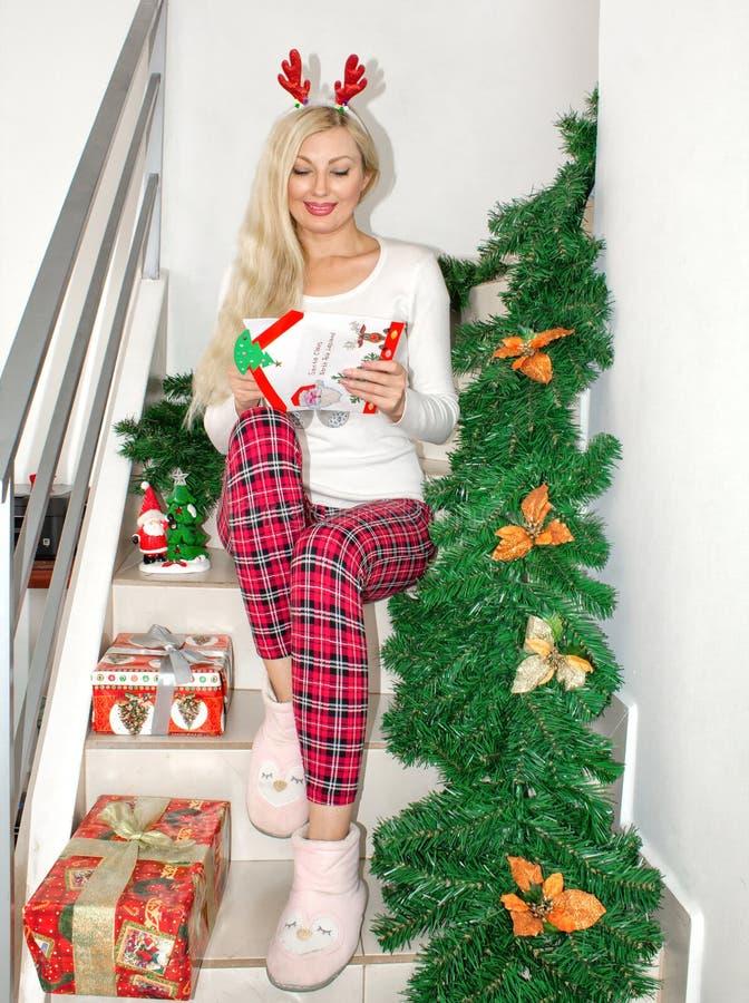 Uma mulher loura nova bonita em pijamas do Natal e com os chifres da rena, sentando-se nas etapas, decoradas com ramos do abeto fotos de stock