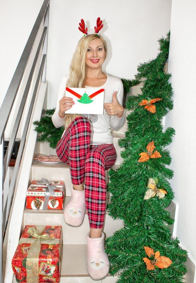 Uma mulher loura nova bonita em pijamas do Natal e com os chifres da rena, sentando-se nas etapas, decoradas com ramos do abeto e imagem de stock