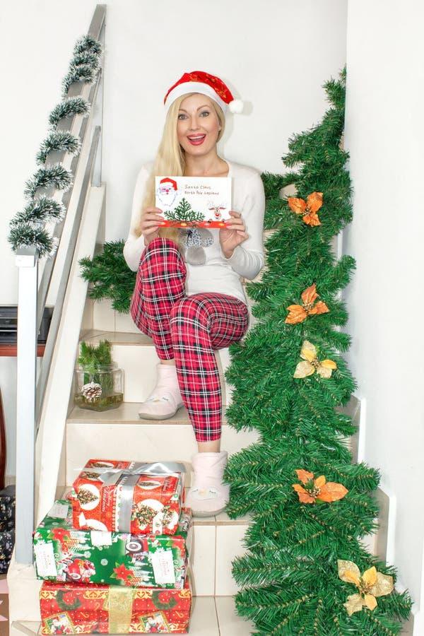 Uma mulher loura nova bonita em pijamas do Natal e com um chapéu de Santa que senta-se nas etapas, decoradas com ramos do abeto e imagem de stock