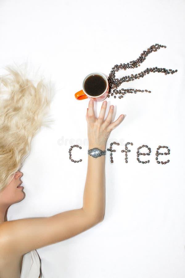 Uma mulher loura nova com cabelo longo estica para fora sua mão com um pulso de disparo estica sobre uma xícara de café, em um fu fotografia de stock royalty free