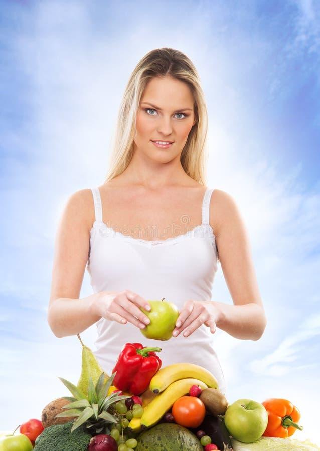 Uma mulher loura nova e uma pilha de frutos frescos foto de stock royalty free