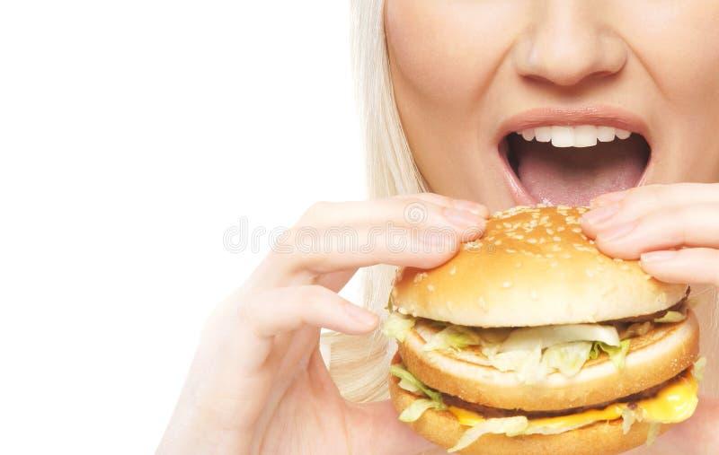 Uma mulher loura nova que earing um Hamburger fresco imagens de stock royalty free