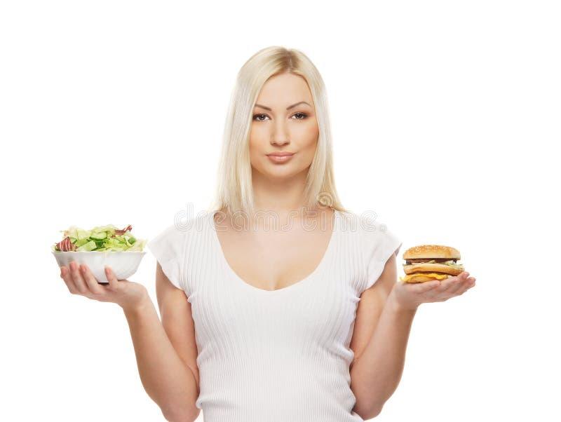 Uma mulher loura nova que prende um hamburguer e uma salada fotografia de stock royalty free