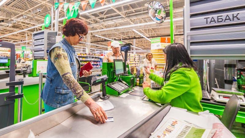 Uma mulher madura bonita está pagando pela compra dos produtos no supermercado pelo cartão de crédito Texto do russo: cigarro fotografia de stock