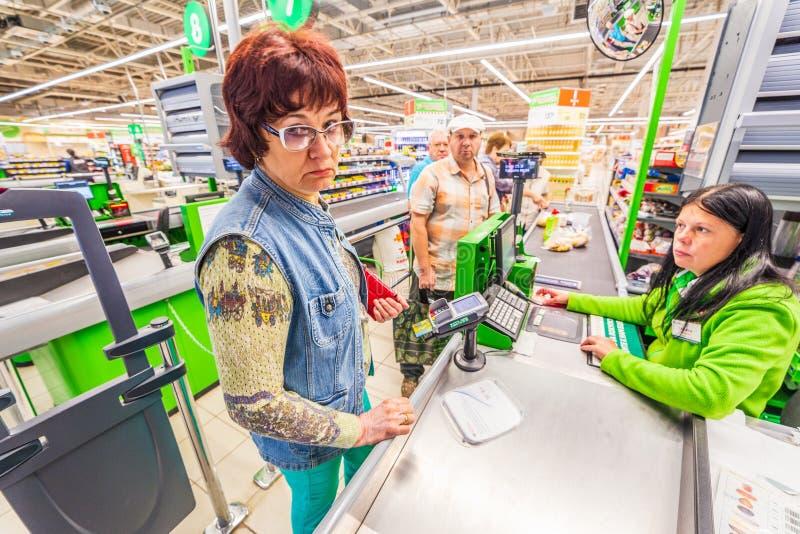 Uma mulher madura bonita está pagando pela compra dos produtos no supermercado pelo cartão de crédito Texto do russo: cigarro imagens de stock royalty free
