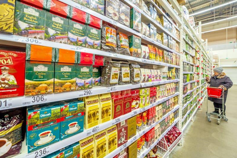 Uma mulher madura bonita pensou sobre o supermercado de compra do chá Texto no russo: o chá, preto, pode, desconto imagem de stock