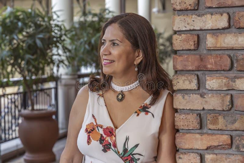Uma mulher madura do latino sofisticado inclina-se em uma parede de tijolo que olha afastado fotos de stock