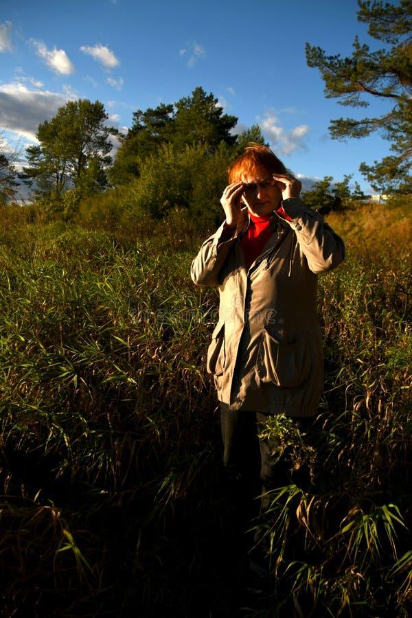Uma mulher madura entre a vegetação luxúria fotografia de stock royalty free