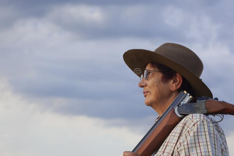 Uma mulher mais idosa com seu rifle olha o por do sol imagem de stock royalty free