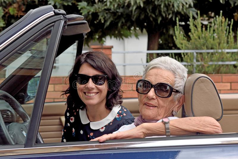 Uma mulher mais idosa e uma jovem mulher que conduzem um convertible imagem de stock