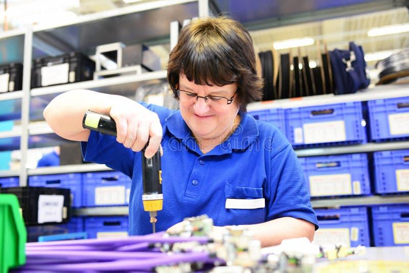 Uma mulher mais idosa monta componentes eletrônicos olá! em uma fábrica da tecnologia imagem de stock royalty free