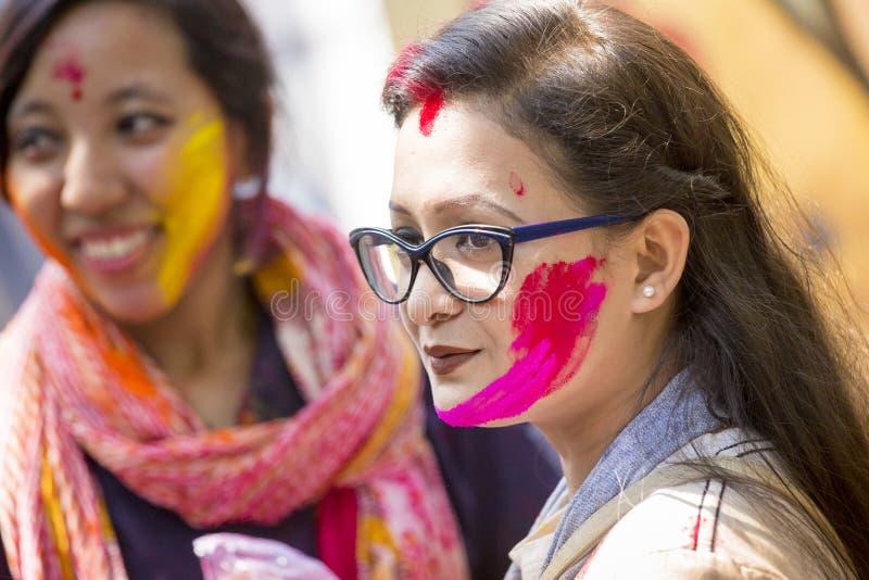 Uma mulher manchada com o pó colorido, participa nas celebrações do festival de Dol Utsav fotos de stock