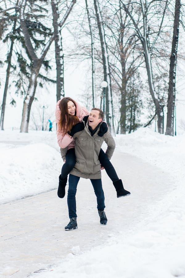 Uma mulher monta um homem em um parque nevado do inverno fotografia de stock royalty free