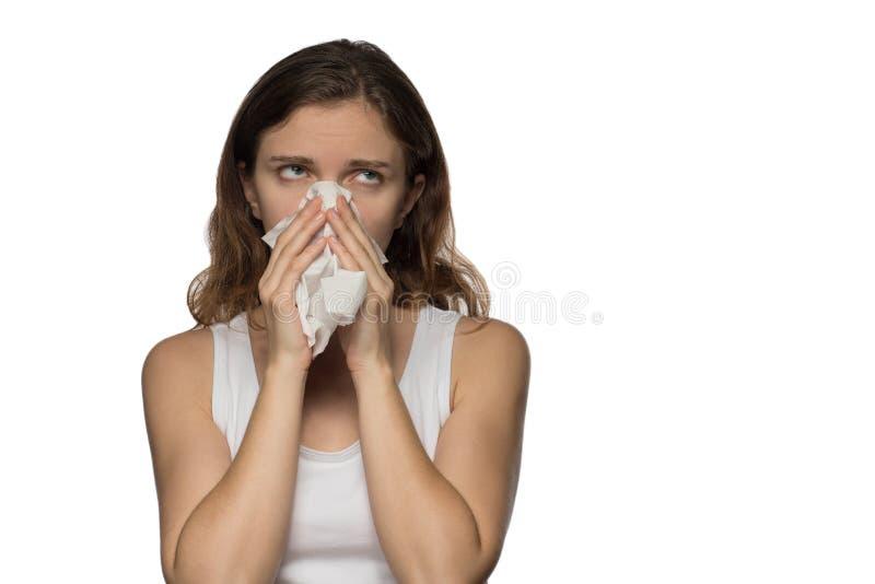 Uma mulher moreno bonita torna-se doente com um nariz frio e ralo, espirros e tosses em um lenço do Livro Branco fotos de stock royalty free