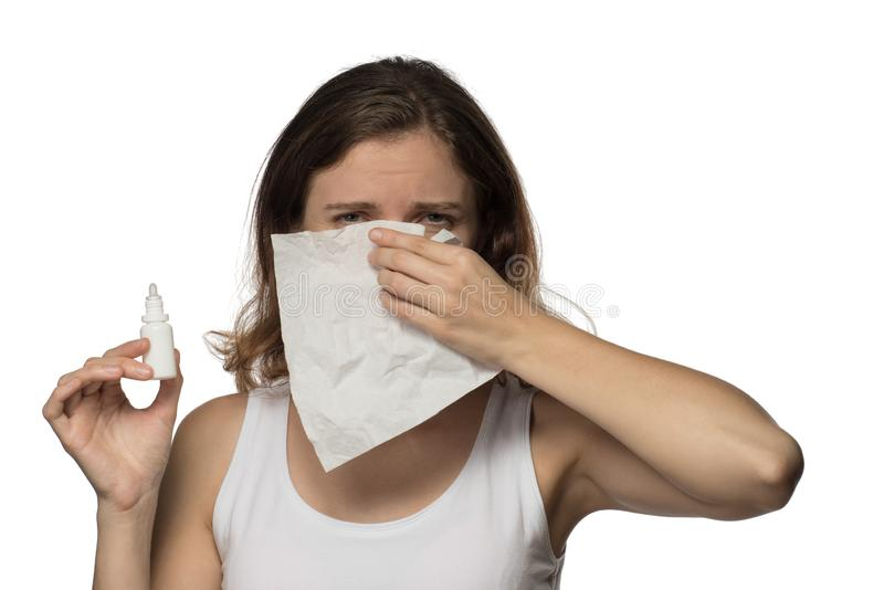 Uma mulher moreno bonita torna-se doente com um nariz frio e ralo, espirros e tosses em um lenço do Livro Branco fotografia de stock royalty free