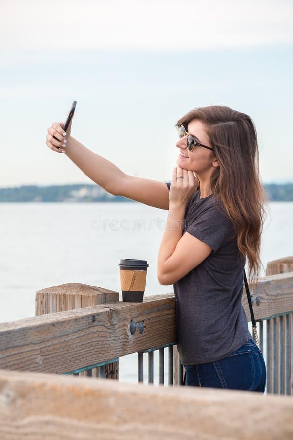 Uma mulher moreno milenar consideravelmente nova com uma tomada do café selfies em um passeio à beira mar do oceano imagens de stock royalty free