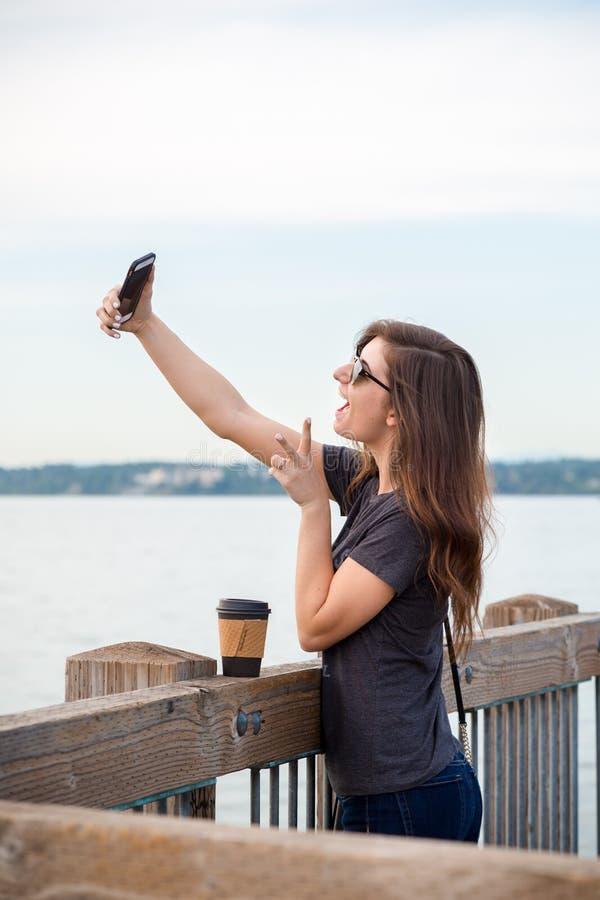 Uma mulher moreno milenar consideravelmente nova com uma tomada do café selfies em um passeio à beira mar do oceano imagens de stock