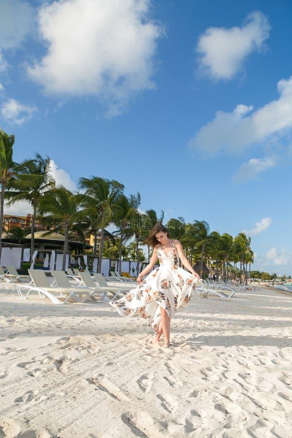 Uma mulher moreno nova atrativa em um vestido branco do verão em uma praia em México fotografia de stock