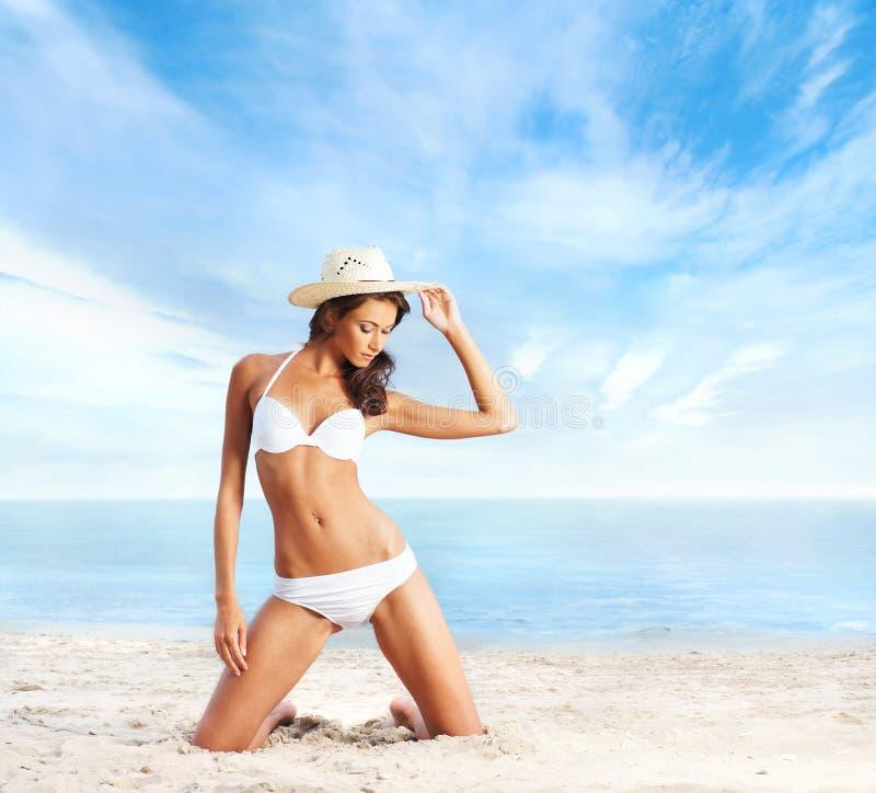 Uma mulher moreno nova em um roupa de banho branco na praia imagem de stock royalty free