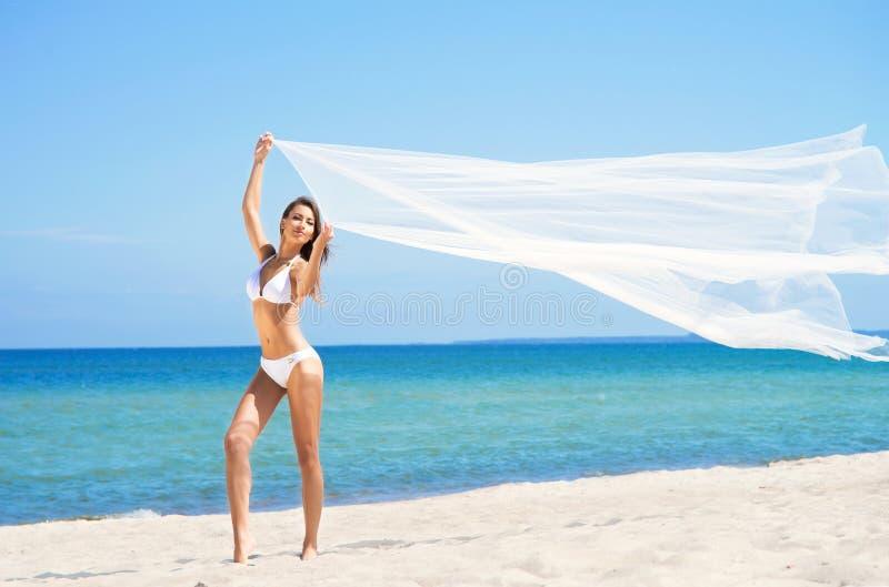 Uma mulher moreno nova em um roupa de banho branco na praia foto de stock