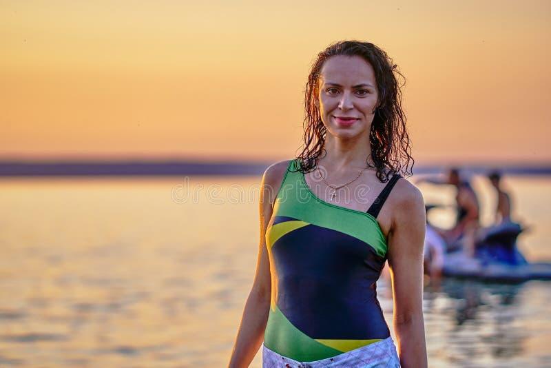 Uma mulher moreno nova em um roupa de banho sai da água após a montada na placa na água de um grande lago foto de stock