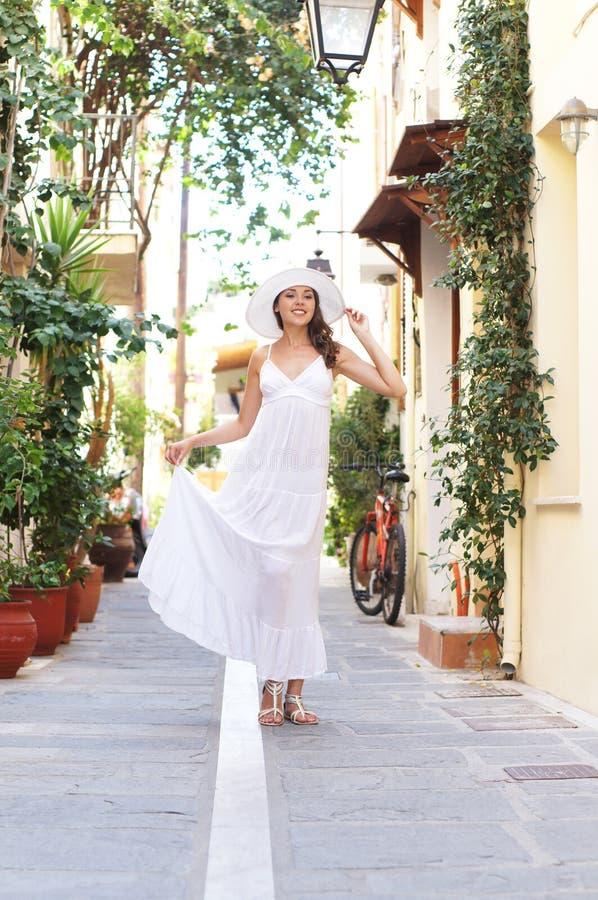 Uma mulher moreno nova em um vestido branco em umas férias fotos de stock