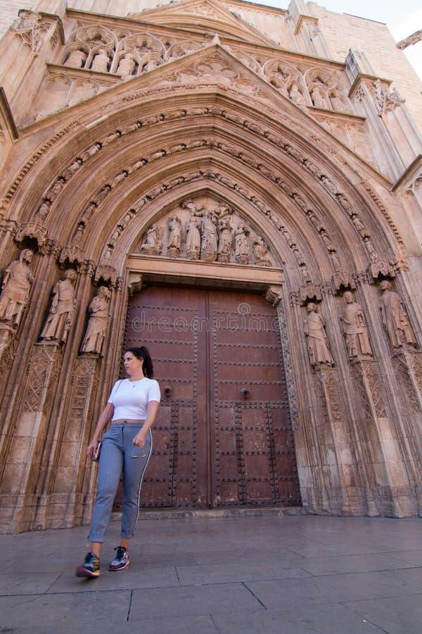 Uma mulher moreno nova que anda na frente da catedral de Valencia Spain com camisa branca e as cal?as cinzentas fotos de stock