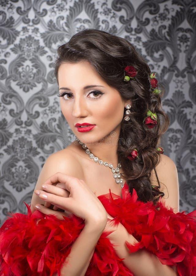Uma mulher moreno nova que guardara penas vermelhas imagens de stock