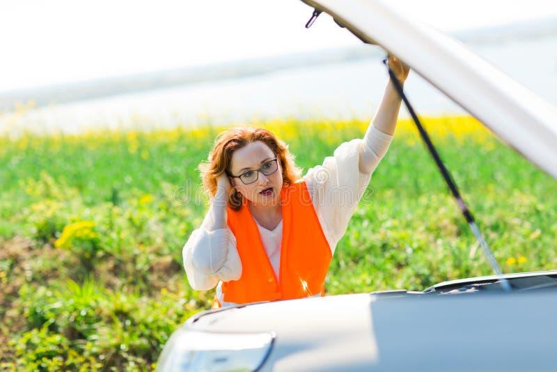 Uma mulher na capota aberta do carro da veste alaranjada de carro quebrado imagem de stock royalty free