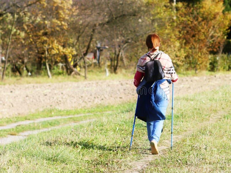 Uma mulher na roupa da cidade dá uma volta através da grama do ` s do verão nos raios de luz solar Estilo de vida saudável Evento imagem de stock