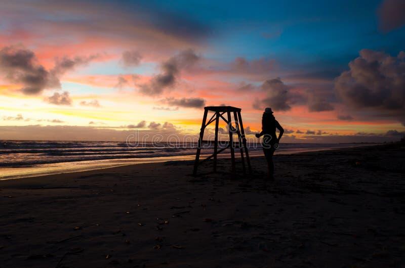 Uma mulher na silhueta ao lado de uma torre da salva-vidas em uma praia com aumentação do sol e os raios de sol que pintam o céu  fotografia de stock royalty free