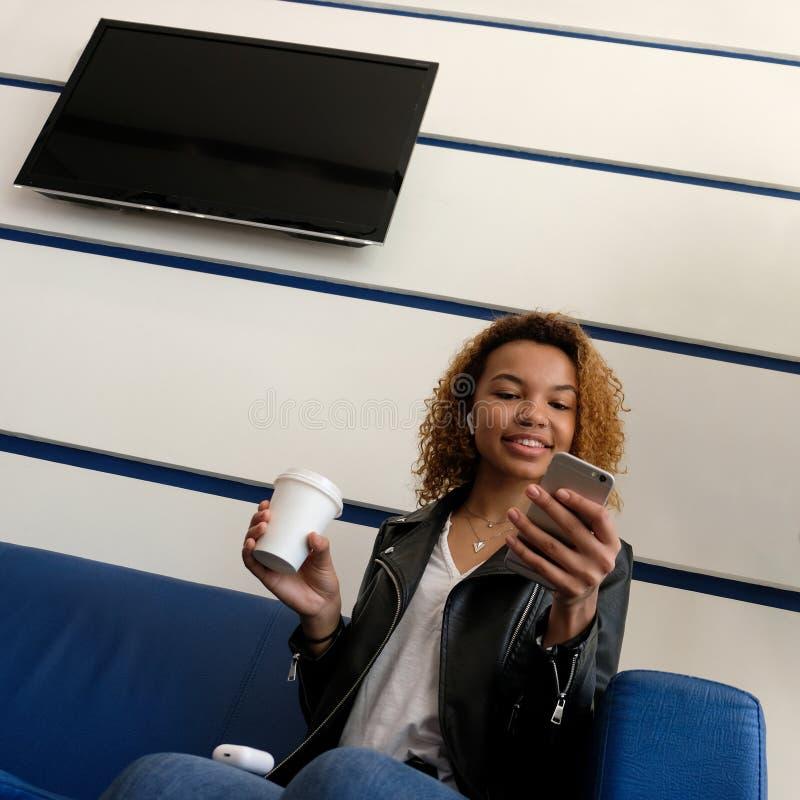 Uma mulher negra moderna nova bonita, em um casaco de cabedal com airpods em sua orelha, escuta a música Para fazer o modelo Tevê fotografia de stock